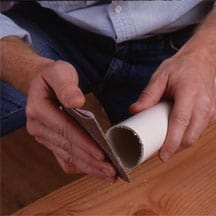 Man's hands sanding a rough PVC pipe edge.