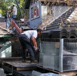 Conveyor belt delivers concrete tile roofing from truck bed to rooftop.