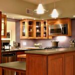 This kitchen employs various types of lighting to achieve a warm, sophisticated ambiance.