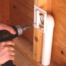 Man's hand screwing a wall-mounting bracket against a stud.