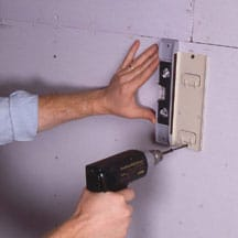 Man's hands screwing a mounting plate against a wall.
