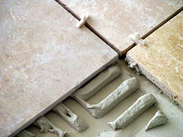 This closeup view shows tile spacers and thinset mortar used for setting tile.