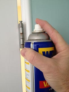 wd-40 spraying door hinge