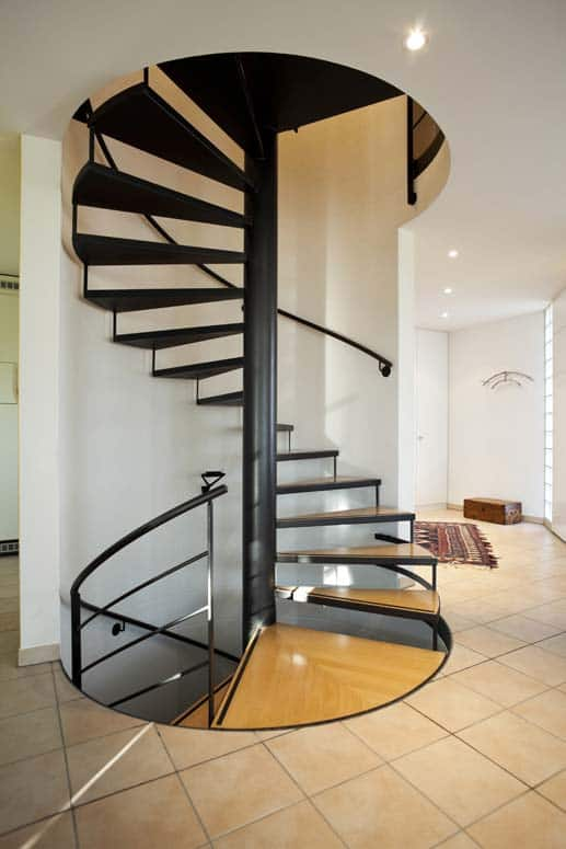 Contemporary design of this spiral staircase is accented by black steel, hardwood, and sweeping lines.