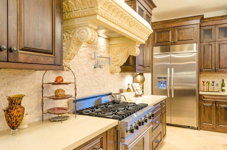 Ornate range hood encloses built-in range equipment.
