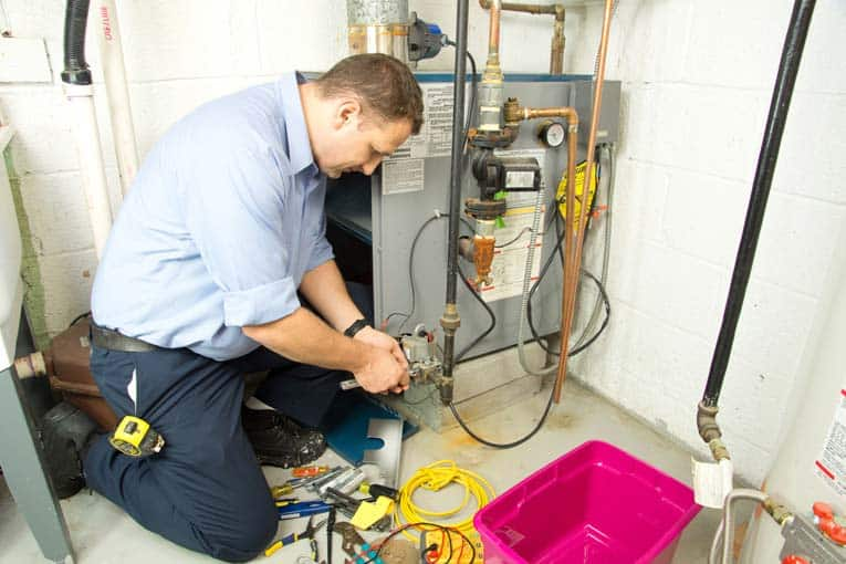 A technician using diagnostic tools on a home furnace in the basement.