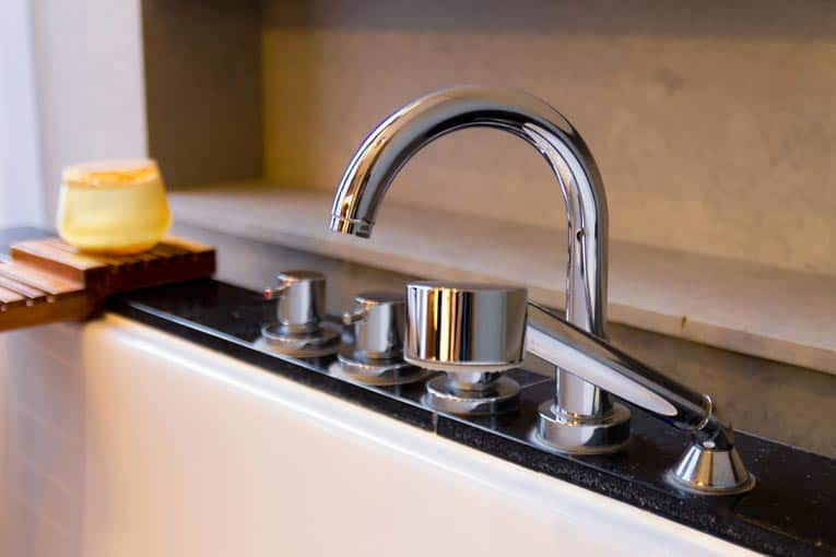 Deck-mounted arching bathtub faucet is located at the side of the tub. This set includes a personal sprayer.