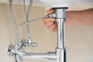 The pivot rod beneath the sink connects the pop-up to the sink-top lever.