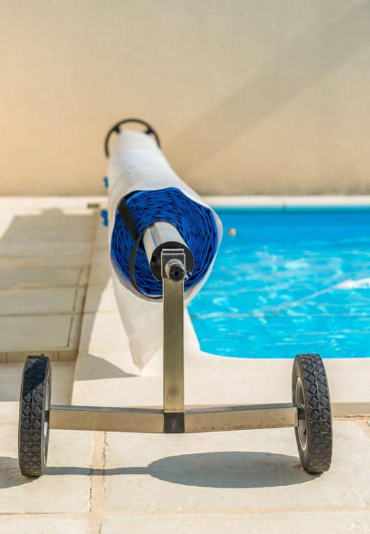 Portable swimming pool cover rolls up on a wheeled carriage and can be moved out of the way when swimmers are in the pool.