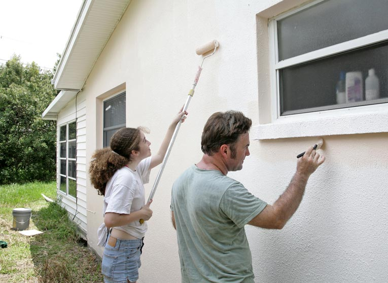 painting house with roller and brush
