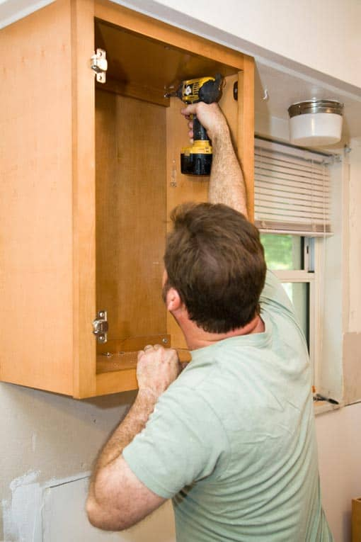 Screw through structural parts of the cabinet back into wall studs for solid support.