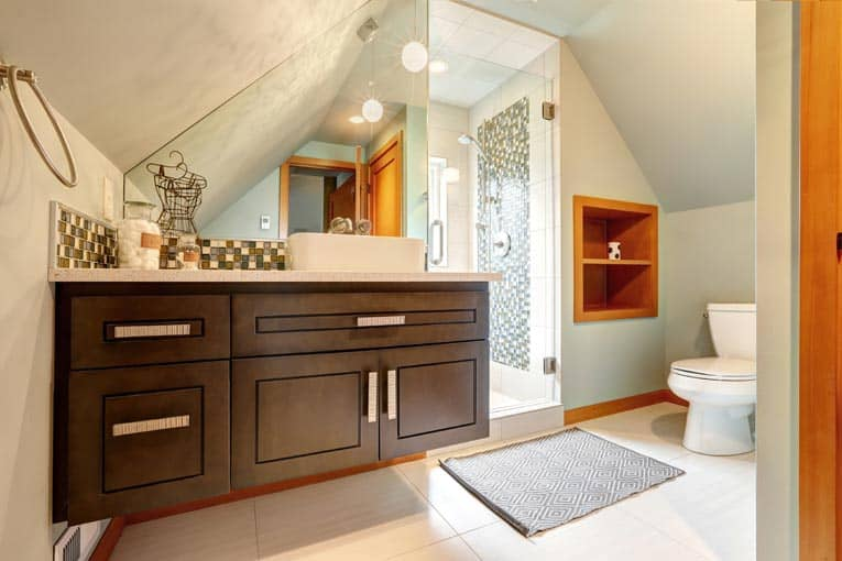 Custom cabinets wedge into an angled nook in this attic bathroom, making maximum use of the available space.