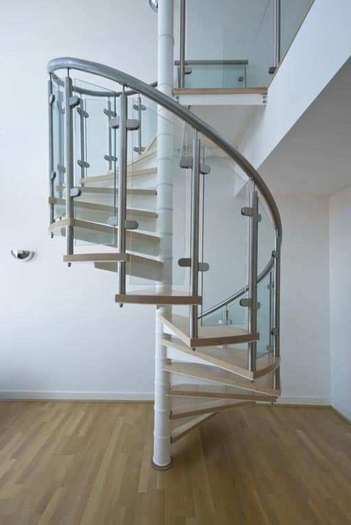 This spiral stair features a combination of structural metal, wood treads, and glass railings.