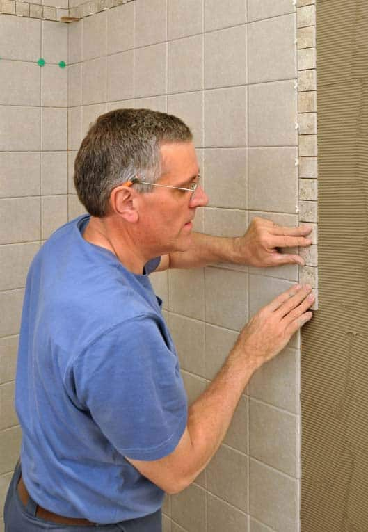 A band of smaller border trim tiles add visual interest to this shower wall.