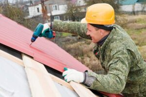 Metal roofing installer screws panels to wooden battens.