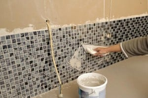 Grout is applied after the tile has been attached to the wall.