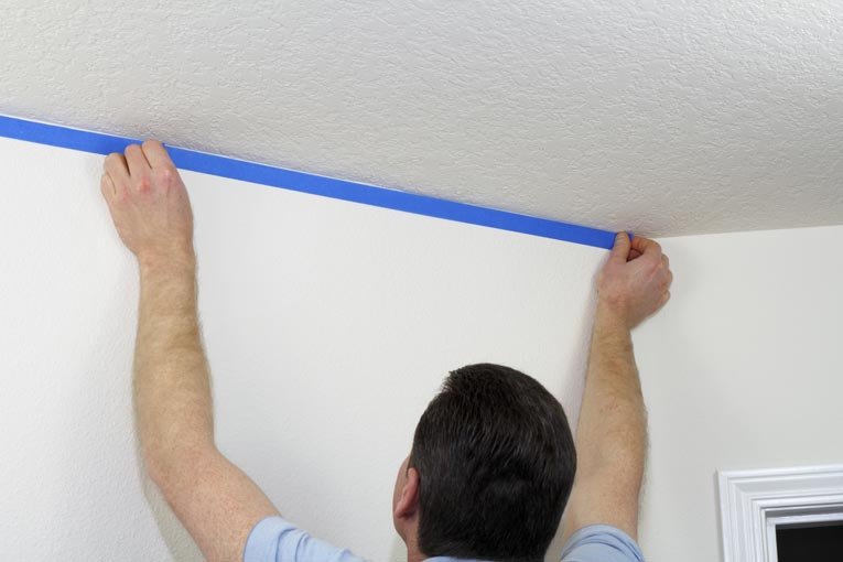 To prevent lapping paint onto walls before painting a ceiling, run a strip of painter's tape along the top of the wall.