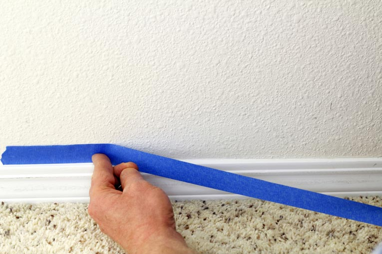 When painting base trim, use painter's tape to mask the wall.