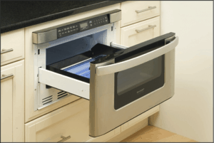 An opened microwave oven drawer below a kitchen countertop.