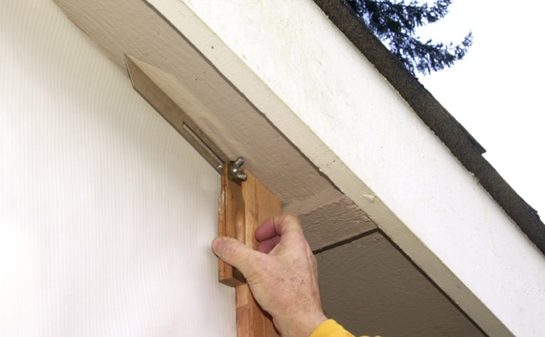 Use a sliding T-bevel to transfer the angle of the roof to the siding boards for making the necessary cuts.