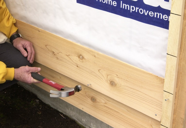 Position and nail the next siding board, placing and spacing nails as recommended by the manufacturer.