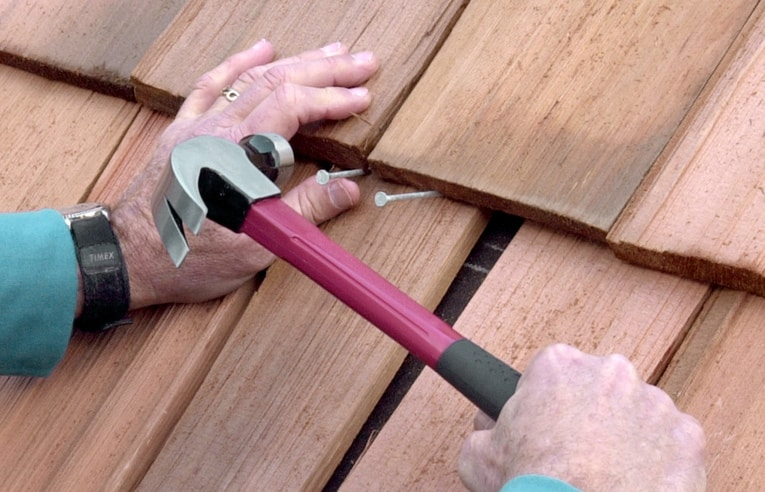 Fasten the shingle with two roofing nails, angled upward. Then tap the shingle up into place.