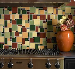 A jumbled pattern of contrasting decorative tiles makes this backsplash a focal point in the kitchen.