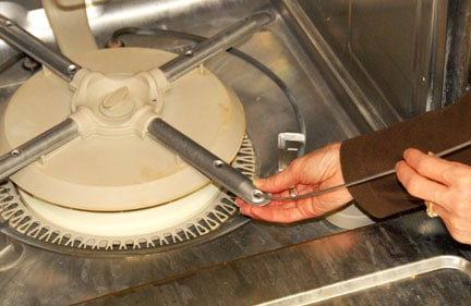 Man's hands cleaning a dishwasher's bottom spray hole with a stiff wire.