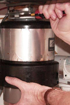 Man's hands turning a garbage disposal's top using a screwdriver.