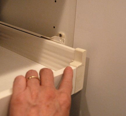 Man's hand holding a white sliding shelve with a missing mounting screw.