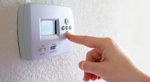 Man's finger pressing a wall-mounted electronic thermostat button.
