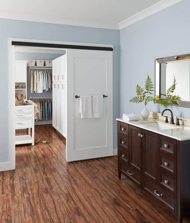 White sliding barn door, leading from a bathroom into a closet.