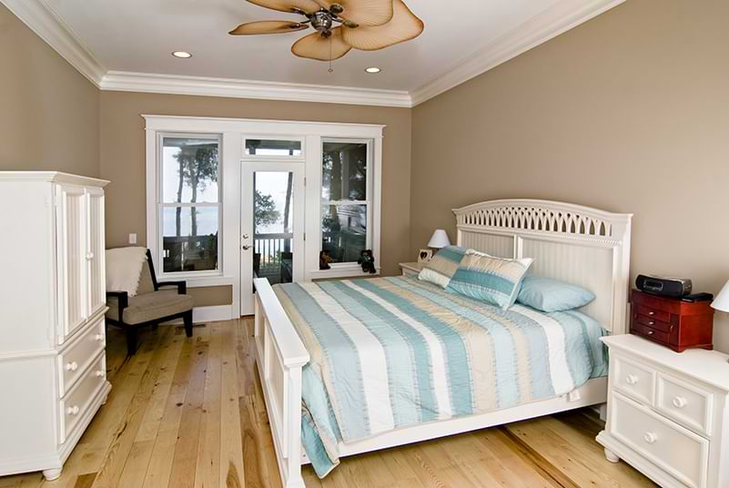 A beach house bedroom with wood floors, crown molding, and tropical ceiling fan.