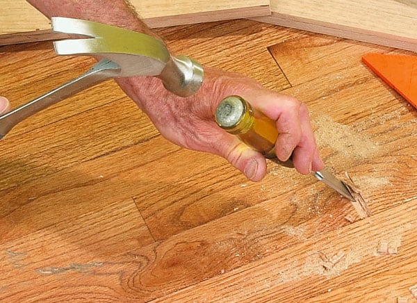 Man's hands hammering a chisel, cutting out part of a wooden floor.