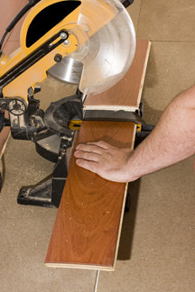Man's hand cutting a hardwood plank using a power miter.