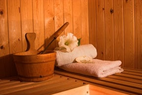 A wooden bucket, ladle, and towels on a sauna's bench.