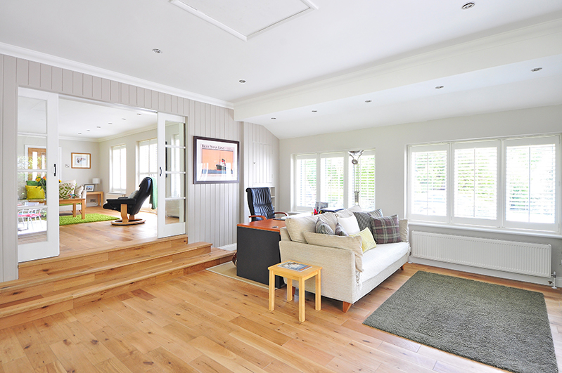 A bright room featuring a white couch, light wood flooring, and lots of windows.