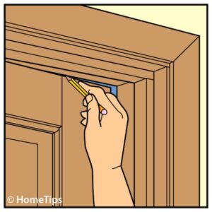Illustration of a man's hand, marking a door's top rail using a pencil.
