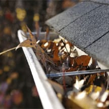 House's aluminum rain gutter filled with dried leaves.
