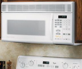 A white over-the-range microwave oven, fitted into an upper cabinet.