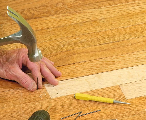 Man's hands nailing a replacement wooden floor board.
