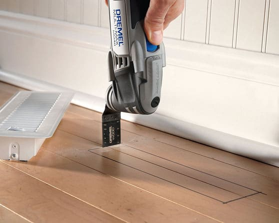 An oscillating multi-tool, plunge cutting a wooden floor for a heating vent.