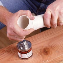 Man's hands connecting an elbow and pre-cut pipe.