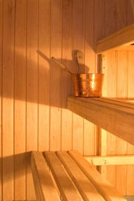Light-colored wooden benches inside a sauna.