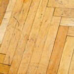 A heavily scratched wooden herringbone floor.