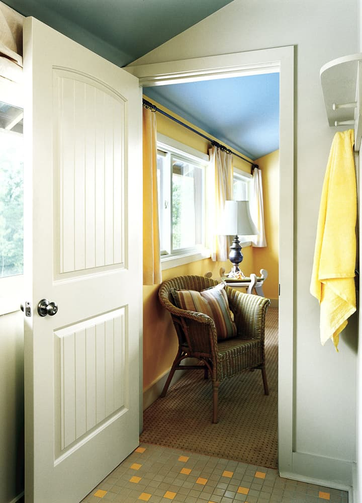 An interior composite door leading from the bathroom into a bright bedroom.