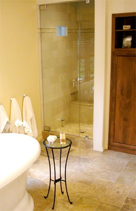 An all-glass steam shower door at the corner of a bathroom.