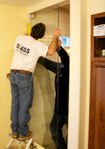 Two men installing a steam shower's glass door inside a bathroom.