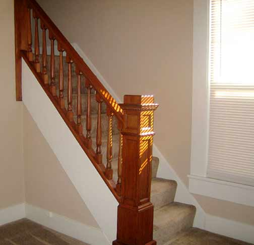 carpeted staircase with wood rail