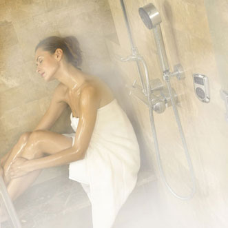 Woman sitting inside a steam shower room.